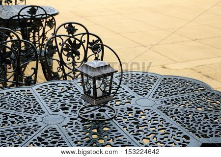 vintage lantern with chairs and table, outdoor restaurant