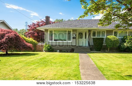 Average North American residential house with concrete pathway over front yard on sunny day in British Columbia