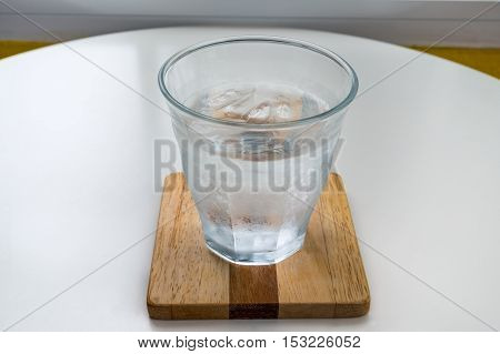 Glass of water on a wooden table.
