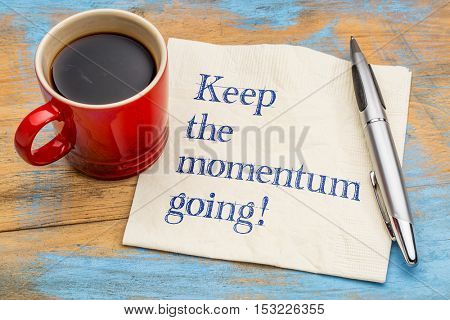 Keep the momentum going - handwriting on a napkin with a cup of espresso coffee