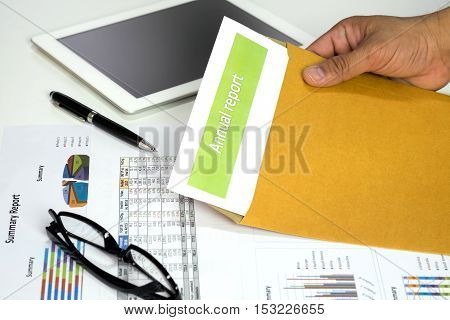 Hand of businessman opening annual report from envelope