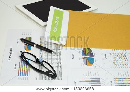 Annual report from envelope with smart tablet, glasses and ball pen