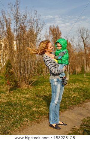 Mom hugging her son in the autumn park. Family time. Happiness of childhood and motherhood. Outdoor Activities.