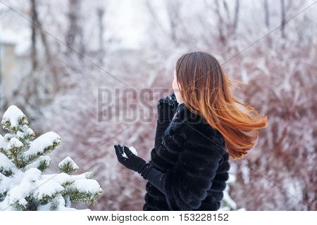 Sweet attractive girl in a fur coat and gloves in the winter park. Winter fun. Walks in the open air. Flying hair.