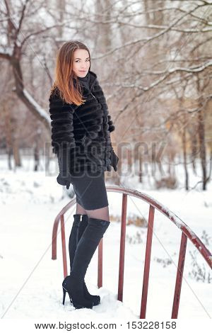 Portrait of pretty attractive girl in fur coat and gloves in the winter park. Winter fun. Walks in the open air. A girl in high-heeled boots.