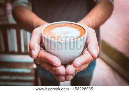 A picture of young man holding a cup of coffee in coffee shop - Vintage style