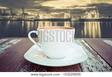 Hot coffee on old wood table with blur background of crane bridge in shipyard - soft focus