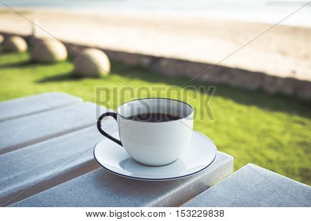 Coffee cup and saucer on wooden table with beach sea view background in Thailand.