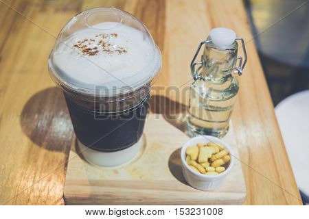 Iced coffee covered with whipped cream in plastic glass and syrup on wooden table at cafe. Vintage style