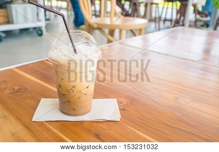 Cold coffee on brown wooden table at cafe. (soft focus)