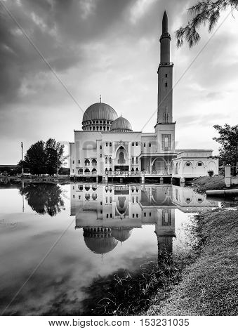 View and reflection of Assalam Mosque with blue skies and white cloud in black and white.
