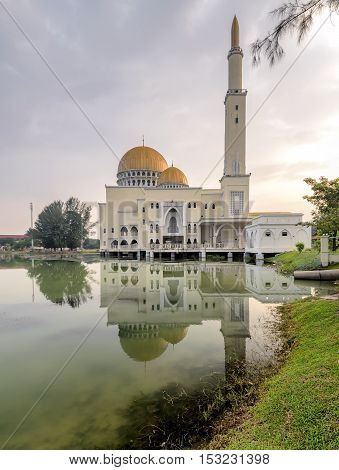 View and reflection of Assalam Mosque with blue skies and white clouds.