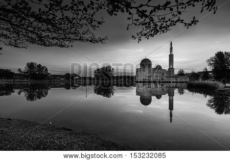 View and reflection of Assalam Mosque with blue skies and white clouds in black and white.