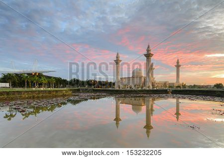 View and reflection of Bukit Jelutong Mosque with stunning blue and red clouds and ray of lights during sunrise.