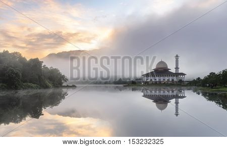 View and reflection of Darul Quran Mosque with fogs and stunning clouds during sunrise.