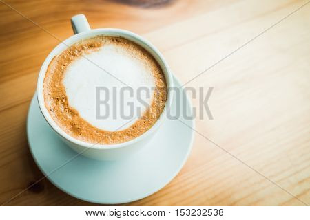 Hot latte coffee cup on wooden table at cafe. Top view