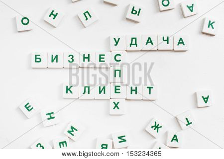 Scrabble words in russian, business concept. Featured words are: Customer, Business, Success, Luck. White background, lot of single letters, white background