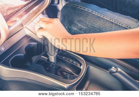 Woman driving car shifting the gear stick. Vintage filter process style