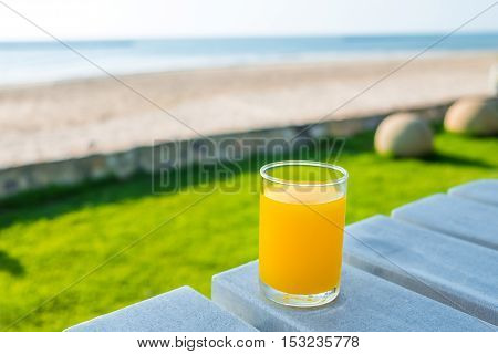 Fresh orange juice on wooden table with the beach background - Solf Focus