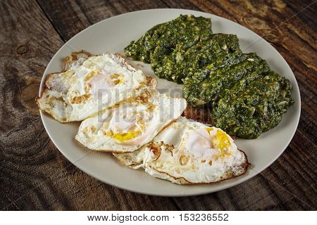 Closeup of fried eggs with spinach side dish