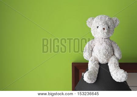 teddy bear sit on the black lamp at headboard and green wall background for gift and surprise