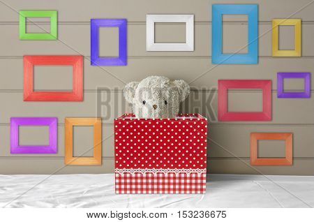 teddy bear doll in red gift box on the white bed with blank multi-color or fancy picture frame at the headboard and brown wall background for gift and surprise