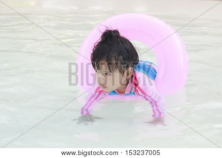 Children or baby girl play in the swimming pool or water park with wearing pink life ring