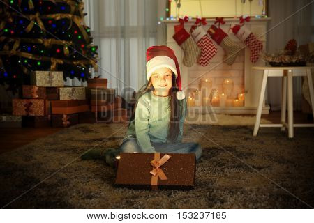 Cute little girl in Santa hat with Christmas present at home