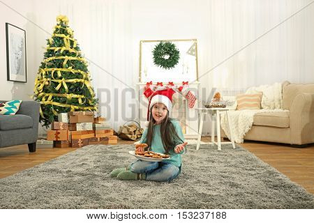 Cute little girl in Santa hat with plate of delicious cookies at home