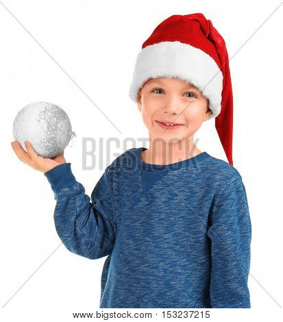 Cute little boy in Santa hat with Christmas ball on white background