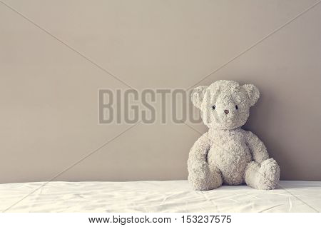 vintage teddy bear sit on the right side white bed at headboard and brown flat wall background for gift and surprise