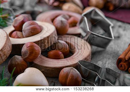 Close up view of cookie cutter, hazelnuts and natural decor on wooden background