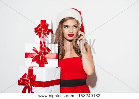 Portrait of a smiling young woman in red santa claus dress and hat holding stack of presents and talking on mobile phone isolated on the white background