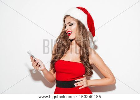 Cheerful pretty woman in red dress and hat using mobile phone and looking away isolated on the white background