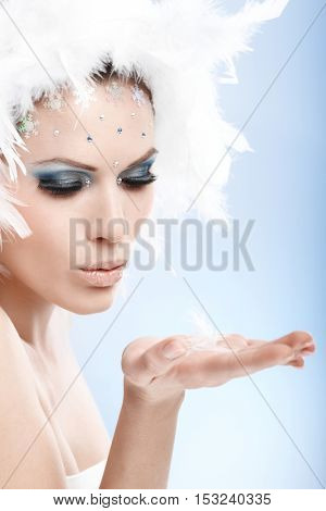 Winter beauty sending a kiss in white feather cap and fancy makeup.