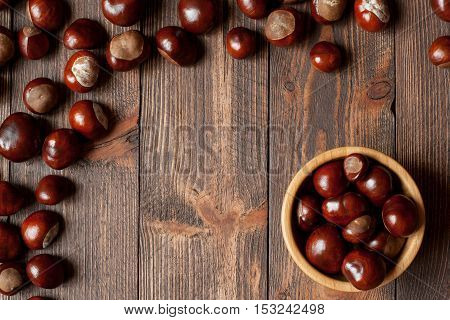 Pile of horse chestnuts on a bamboo bowl on wooden table