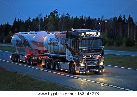 SALO, FINLAND - OCTOBER 21, 2016: The latest super bulk transport truck of Kuljetus Auvinen, Mercedes-Benz Actros Uniq Concept, lights up the darkness while trucking along freeway late in the evening.