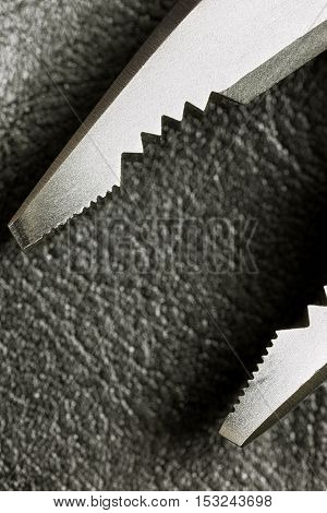Close up Hand Work Tool Pliers. Pliers on a leather surface