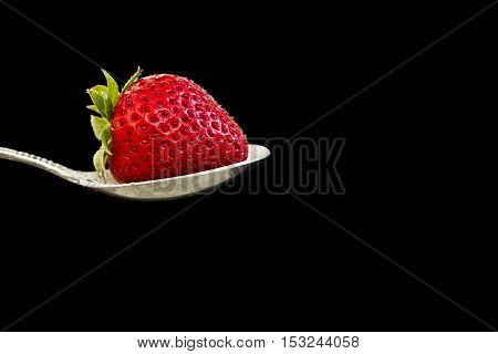 beautiful fresh red strawberry lying in a silver spoon isolated on black