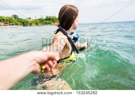 Woman wearing bikini and diving googles dragging her partner to the open sea, they have a vacation together