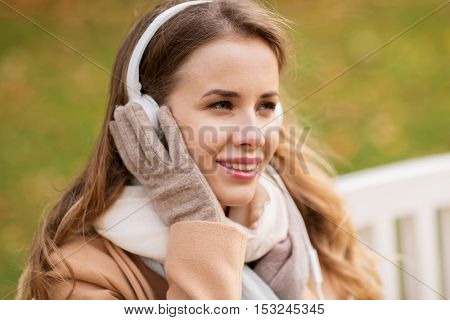 season, technology and people concept - beautiful happy young woman with headphones listening to music and sitting on bench in autumn park