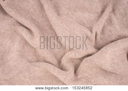 close up beige knitted pullover background. Top view.