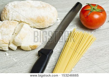 sliced bread with loose flour and tomatoesspaghetti on a wooden board