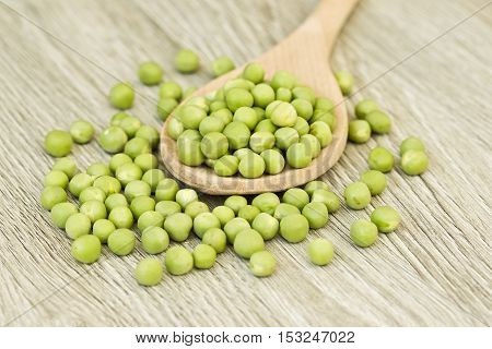 Fresh green peas in a wooden spoon on a textured wooden board