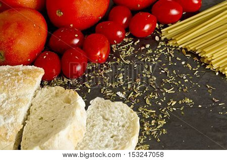 Tasty Italian spread with tomatoesbread spaghetti and spices on a board with selective angled lighting