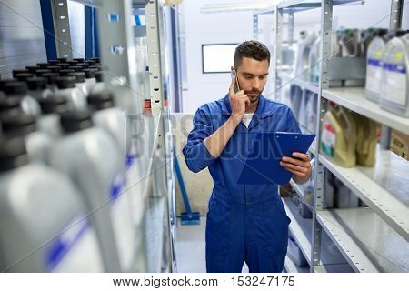 car service, repair, maintenance and people concept - auto mechanic man or smith with clipboard calling on smartphone at workshop or warehouse