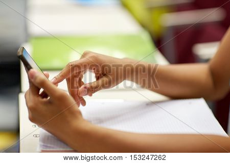 education, high school, university, learning and people concept - close up of african student girl hands with smartphone on lecture