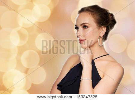 people, luxury, jewelry and fashion concept - beautiful woman in black wearing diamond earrings and bracelet over holidays lights background