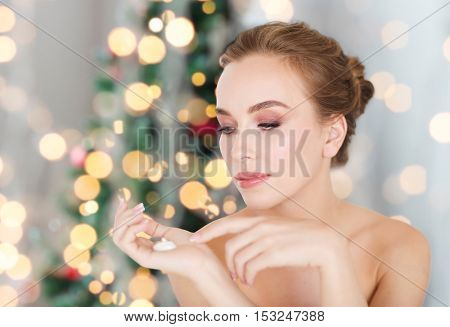 beauty, people, holidays, skincare and cosmetics concept - young woman with moisturizing cream on hand over christmas tree lights background