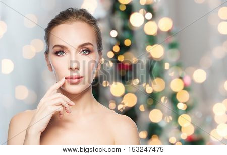 beauty, people, holidays and plastic surgery concept - beautiful young woman showing her lips over christmas tree lights background